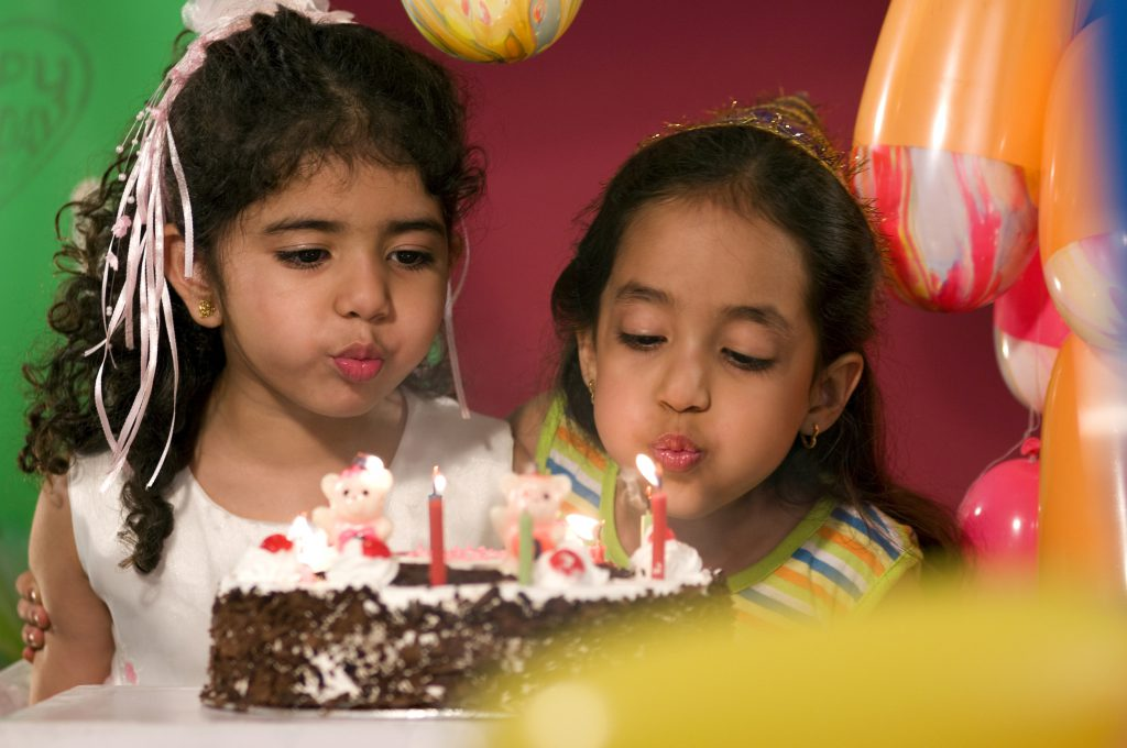 Two girls blowing out candles